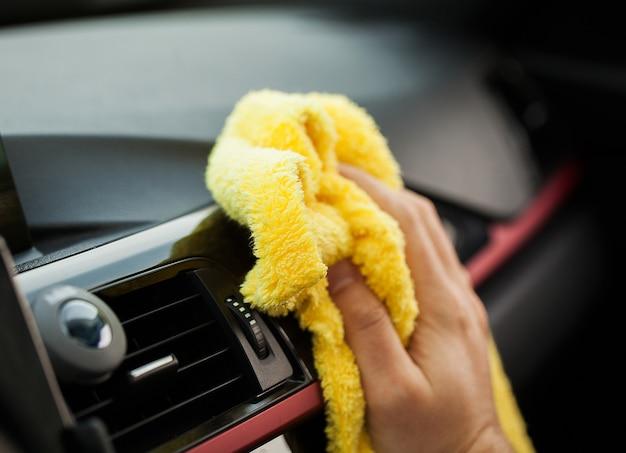 清掃車車内を洗浄するマイクロファイバーの布で手