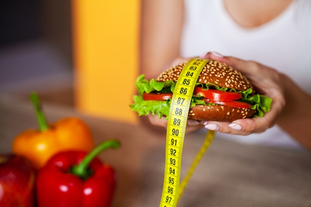 密封された口を持つダイエット女性の概念は脂っこいハンバーガーを保持します