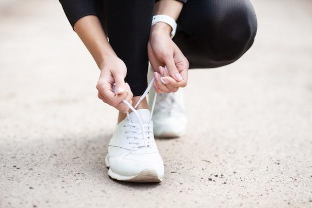 スニーカーの問題ジョギングの準備をして彼女の靴を結ぶ女性ランナー