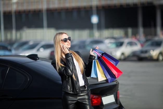 黒い金曜日の休日に彼女の車の近くの色のバッグを保持している女性。