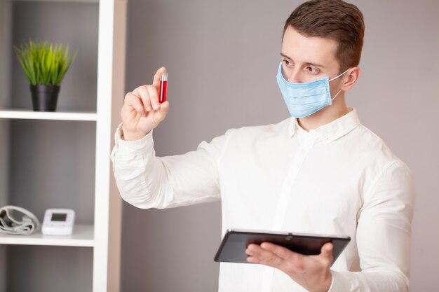 ウイルス検査で試験管を保持している若い医者