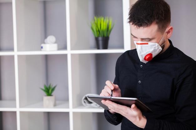 Человек в защитной маске работает на планшете в офисе