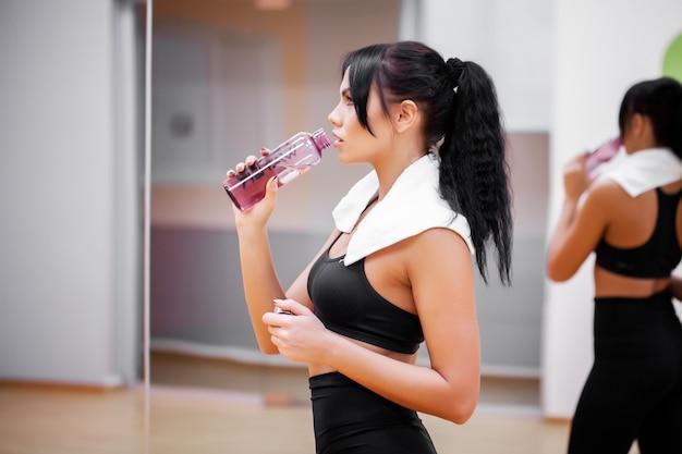 Фитнес девушка. молодая красивая женщина в спортивной питьевой воде.