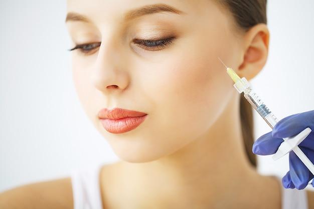 Инъекции пластической хирургии губ на лицо молодой женщины