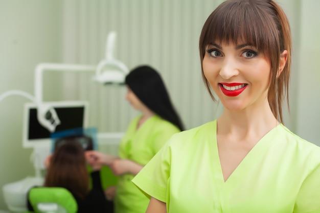歯科医の男性は歯科医院でクライアントに歯を治療しています