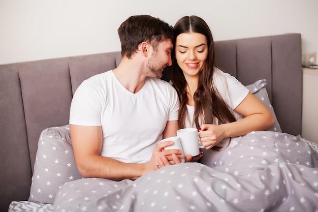ベッドで楽しんで幸せなカップル。お互いを楽しんでいる寝室で親密な官能的な若いカップル