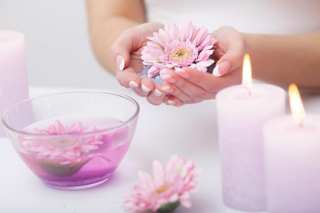 Уход за ногтями. крупным планом красивая женщина руки с натуральными ногтями в салоне красоты. женские впитывающие ногти в прозрачной стеклянной миске, полной воды в помещении. спа маникюр концепция. высокое разрешение