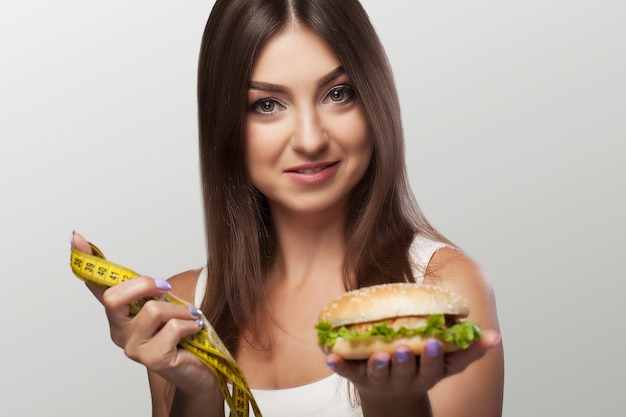 Вредная еда. молодая девушка борется с лишним весом и вредной едой. выбор между похуданнам и бургером. концепция здоровья и красоты.
