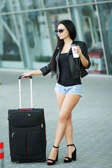 Женщина едет путешествовать с багажом во львовский международный аэропорт и пить кофе
