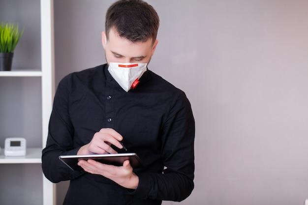 Человек работает в офисе в маске для защиты от коронавируса