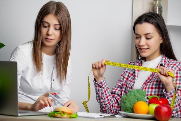 Женщина в белом халате диетолога пишет программу здорового питания для похудения