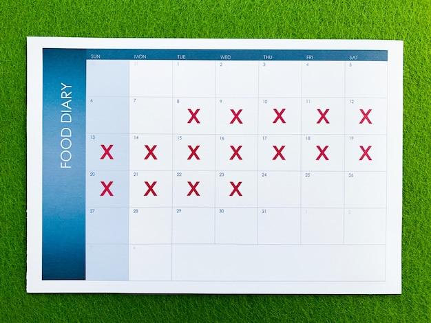 緑の背景にダイエット計画カレンダーを文書化します。