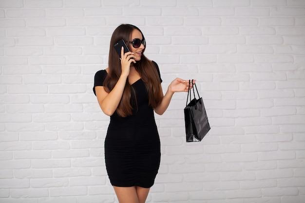 Женщина держа сумку в черном празднике пятницы