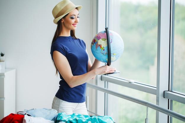 Красивая женщина собирает одежду в чемодан путешествия