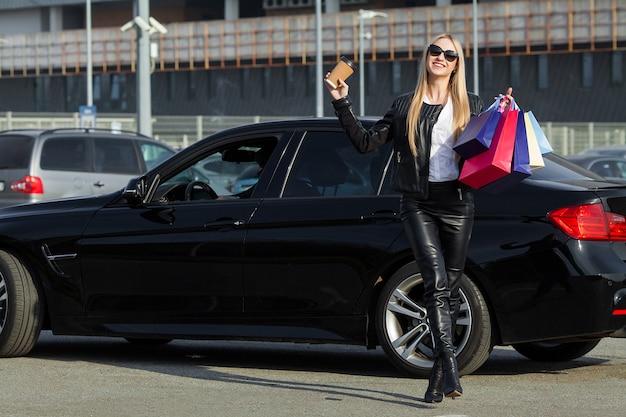 黒い金曜日の休日に彼女の車の近くの色のバッグを保持している女性