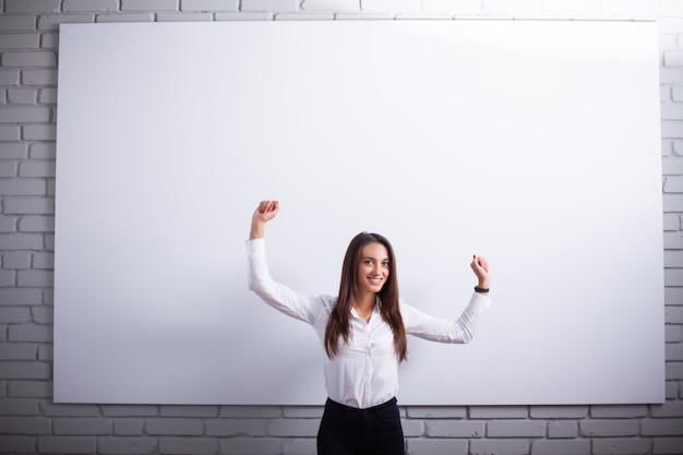 Портрет счастливой молодой женщины коммерсантки близко на белой стене.