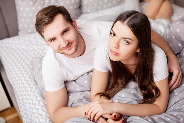 Счастливая чувственная молодая пара, лежа в постели вместе