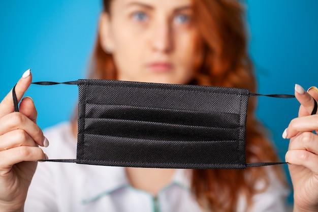 ウイルスから保護するために口と鼻を覆うマスクを保持している女性。