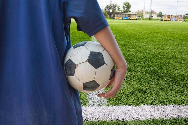 フィールド上にサッカーボールを持つプレーヤー