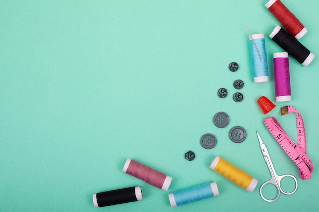 ソーイングキットのアクセサリー。緑色の背景のモックアップフレームトップビューの仕立てとカラフルなスレッド、針、ピン、はさみのツールを設定します。