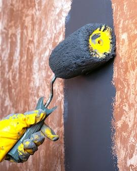 黄色の作業用手袋のローラーで灰色のアクリル絵の具で手塗りの家の壁。