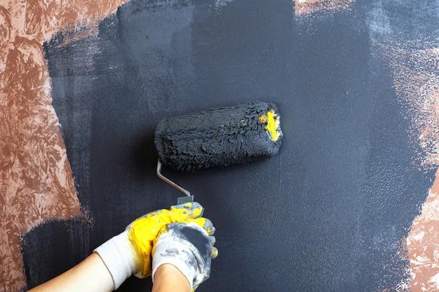 壁をローラーグレーで手塗りします。アパートの修理コンセプト。