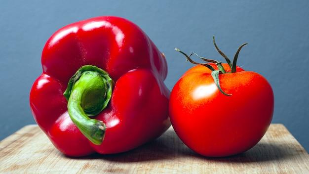 Помидор и красный сладкий перец на деревянной тарелке на сером фоне. свежие здоровые овощи.