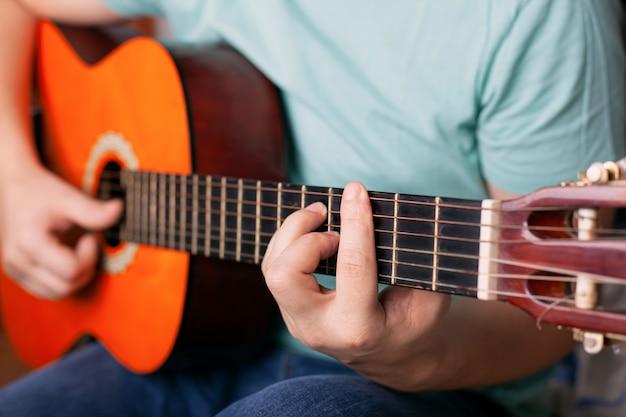 Парень играет на акустической гитаре, мужчина пальцем держит аккорд бар. научиться играть на музыкальном инструменте.