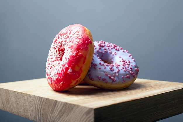 Сладкие разноцветные ассорти пончики с глазурью и порошок на деревянной доске на сером фоне.