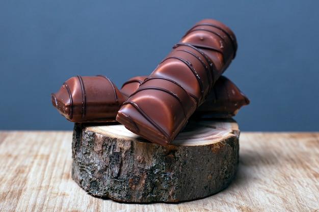 Части конфеты шоколада на куске дерева крупным планом.