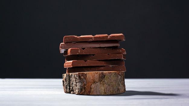 Части молочного шоколада на деревянной стойке на серой предпосылке.