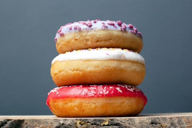Три пончики с цветной глазурью фиолетовый красный и белый с порошком стоят друг на друга на подставке на сером фоне крупным планом.