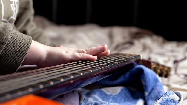 オレンジ色のアコースティックギターの首に子供の手。楽器の演奏を学ぶ。
