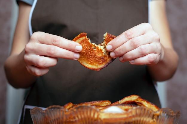 料理人が手に揚げたパンケーキを手に持って味わいます。コンセプト:ホームベーキング。