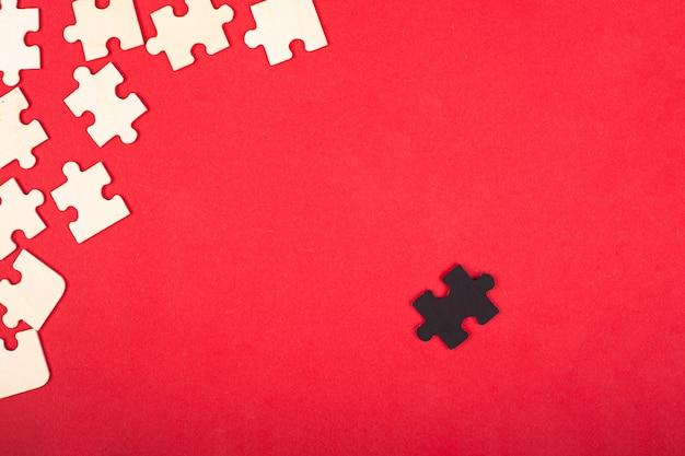 Деревянные белые и черные головоломки на красном фоне крупным планом вид сверху. изгоем антисоциального лидера отличаются от других детские развивающие игрушки.