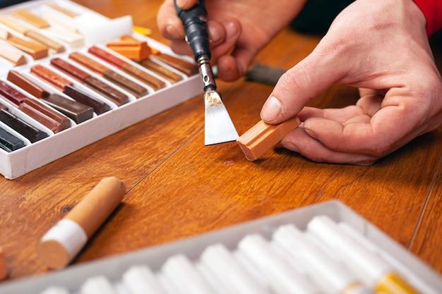 ラミネートと寄木細工の修復は、傷やチップを密封します。マスターはワックス鉛筆のクローズアップで木の表面を修復します。