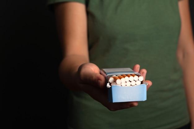 Рука девушки держит пачку сигарет, предлагает сделать выбор. предлагают никотин, табак.