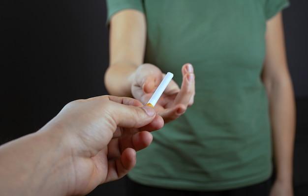 タバコで処理します。男が分かち合っていると、喫煙によって少女に害が及ぶ。