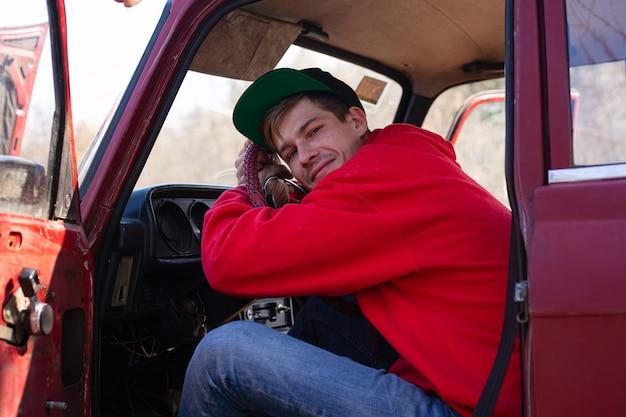 若い男は赤い車の運転席に座って、ステアリングホイールに手します。休暇、旅行、車両の概念