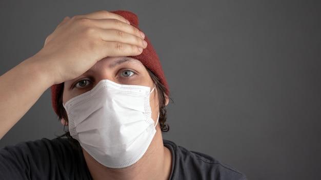 Мужчина трогает лоб, проверяя температуру, подозревает коронавирусный больной.