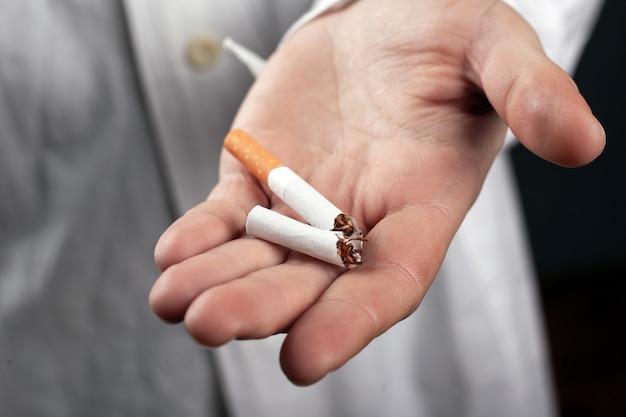Сломанная сигарета в руке у доктора крупным планом. опасности для здоровья от курения табака.