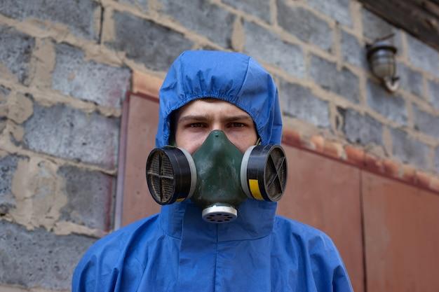 保護用の青いオーバーオールとフェイスマスクの男は、レンガ造りの建物のクローズアップの近くに立っています。