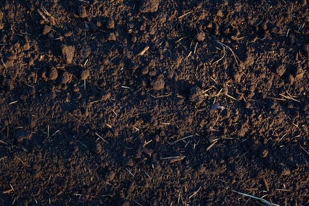 Текстура переваренной черной земли, коричневая предпосылка земли.