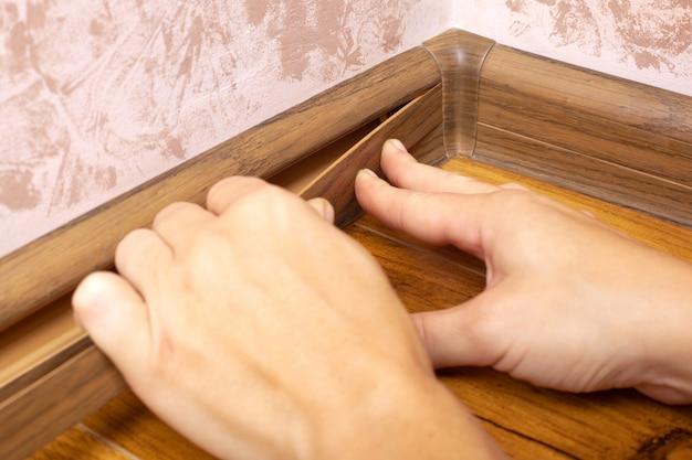 ラミネートの色の床プラスチック幅木のインストール