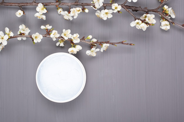 白い桜の花のトップビューコピースペースの枝と灰色の背景にボディスクラブ