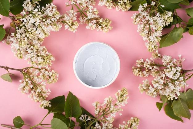 Скраб для тела на розовом фоне среди ветвей белой сирени, вид сверху, красота, уход за кожей, очищение кожи, косметика.