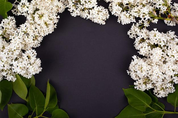 黒い背景の上面、背景に白い咲くライラックの枝