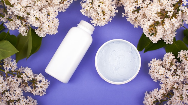 Косметика в белых флаконах на фиолетовом фоне с ветками белой сирени, вид сверху, уход за кожей, красота, очищение и увлажнение тела