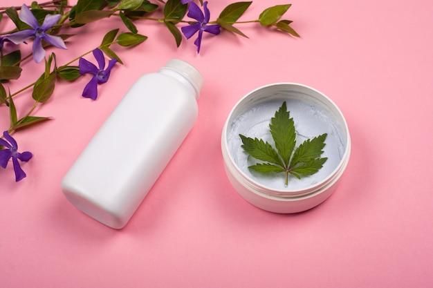 Белые бутылки с косметикой тела с листьями марихуаны на розовом фоне с фиолетовыми полевыми цветами. уход за кожей, красота, косметика с каннабисом