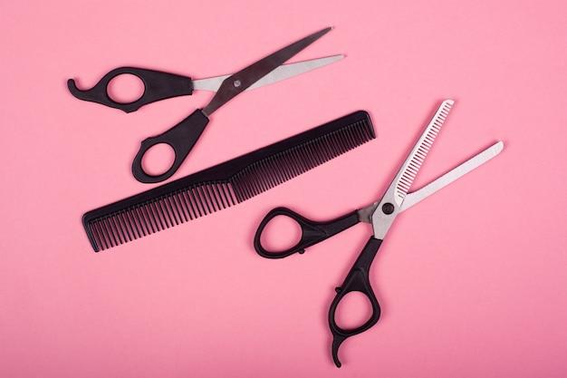 Парикмахерские инструменты, черные ножницы и расческа на розовом столе.